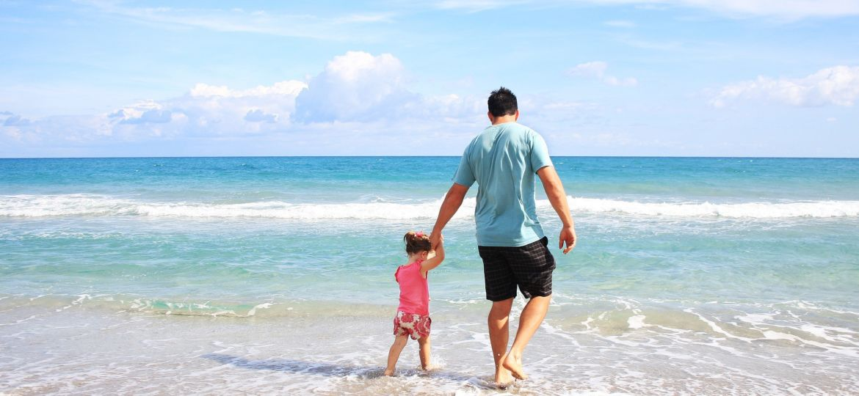 Familia bien asegurada dando un paseo en la playa